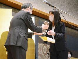 中尾清一郎佐賀新聞社社長(左)からトロフィーを受け取る森山映泉さん=佐賀市のホテルニューオータニ佐賀