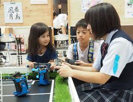生徒に操作方法を教わりながら、サッカーロボットの操作体験をする子どもたち=佐賀市のゆめタウン佐賀