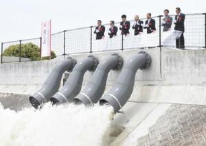 石塚雨水ポンプ場の竣工式で排水を見守る関係者ら=佐賀市諸富町