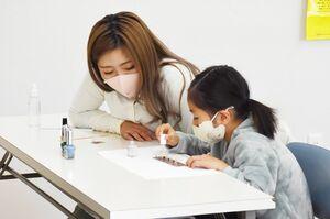 学生のサポートを受けながら、ネイルを体験する参加者=佐賀市唐人のエッジ国際美容専門学校