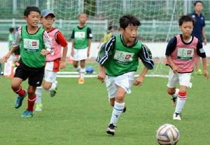 交流試合で軽快な動きを見せる子どもたち=佐賀市の県総合運動場陸上競技場