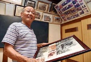 集会所に飾られたロケの写真を手に、当時を振り返る岡了さん=唐津市材木町