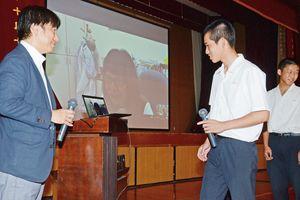 ジャパン・コスメティックセンターの亀石克美チーフコーディネーター(左)が提携する台湾の博士とインターネット電話を通じて英語で話す佐賀農業高の生徒=白石町の佐賀農業高