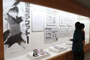 迫力ある複製原画や掲載誌、ラケットなどが展示されている=基山町立図書館