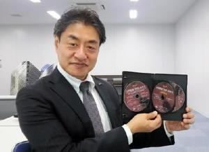 完成した3枚組みDVDを手にする実行委員会事務局長の亀井信一さん