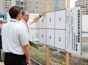 参院選のポスター掲示板の確認をする佐賀市選管の担当者=駅前中央1丁目