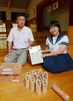 富士町体育協会の原敏朗会長(左)からモルック1セットを受け取った森田花歩さん=佐賀市の富士中