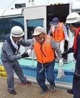 原子力防災訓練でライフジャケットを着て船で避難し、唐津東港に到着した加唐島の島民=9月、唐津市