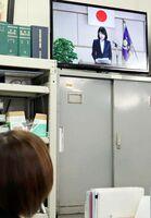 テレビ画面に映った杉内由美子本部長の年頭訓示に耳を傾ける職員(県警提供)