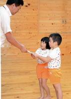 トヨタ紡織九州の馬場崎貴久総務係長(左)が折りたたみテントの目録を園児に手渡した=神埼市の西郷保育園