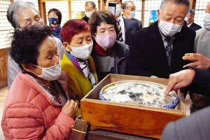 カビの具合を眺める住民=佐賀市川副町の海童神社