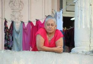 ハバナ旧市街で外を見つめる女性。小さな社会主義国に変革の波が来ている