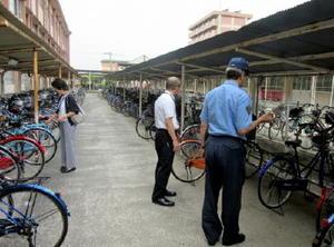 自転車が施錠されているかを調査する署員ら=佐賀市の鍋島中学校(提供画像)