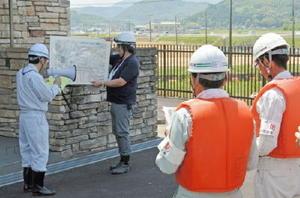 訓練前に遊水池の概要について説明を受ける関係者=多久市の牟田辺遊水池