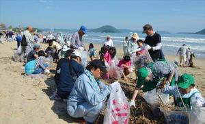 上流の河川から流れ込んだ木切れなどを拾うグループや親子=唐津市東の浜