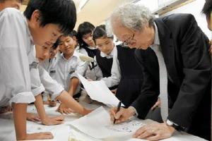 「子ども 夢・アートアカデミー」の後、藪野さんにサインや描いてほしい絵をお願いする児童たち=佐賀市の佐賀大学附属小学校