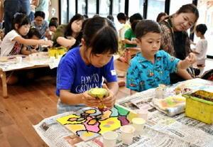 木工用ボンドを使って絵を描く子どもたち=佐賀市水ケ江の「おへそこども園」