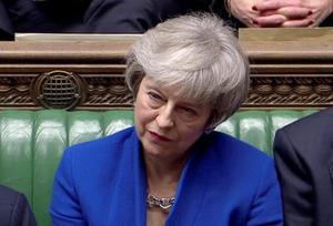 不信任決議案が否決された後、野党労働党のコービン党首の演説に耳を傾けるメイ首相(ロイター・テレビのキャプチャー画像)=16日、ロンドン(ロイター=共同)