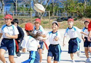 前を走る仲間からのパスを受け取る児童=玄海町の玄海みらい学園