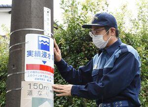 浸水深2・2メートルに合わせて電柱に浸水位置表示板を取り付ける小松政市長=武雄市朝日町