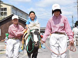 佐賀農業高の生徒のサポートを受けながらポニーに乗る園児=白石町の佐賀農業高