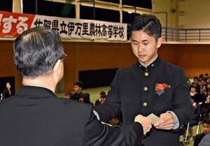 青木久生校長から卒業証書を受け取る伊万里農林高の3年生=伊万里市二里町の同校