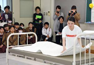 ベッドメイキングでスピードや正確性を競う神埼清明高の堀田眞菜さん(右)=神埼市の同校