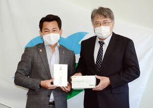 松尾佳昭町長にサージカルマスクを手渡す堤浩範社長(右)=有田町役場