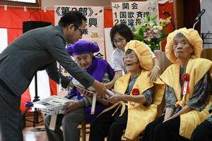 古川政弘施設長から米寿の記念品を受け取り、笑顔を見せる入所者=佐賀市の佐賀整肢学園・佐賀向陽園