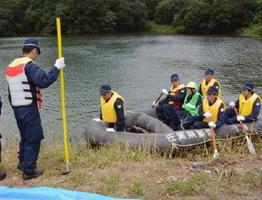 訓練で、対岸に残された孤立者をゴムボートで救助した神埼署員ら=神埼市神埼町尾崎の天神尾池