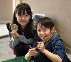 自分たちで作った銅剣や前漢鏡を笑顔で手にする子どもたち=吉野ケ里歴史公園