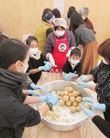 みそ造りに挑戦する参加者=佐賀市の県立図書館南広場