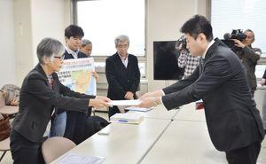玄海原発再稼働同意撤回などを求める要請書を手渡す石丸初美代表(左)=佐賀県庁