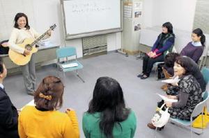 ギターを弾き語り、洋楽の歌詞を解説する西村旬子さん(写真左)=江北町のふれあい交流センターネイブル