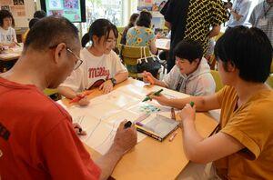 グループごとに理想とする町を考え、用紙に自然や施設を描いていく参加者=佐賀市白山の県国際交流プラザ