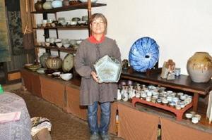 新作の五角形の大鉢を持つ寒鶯窯の田中邦子さん=多久市東多久町