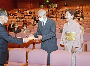 中尾清一郎社長(左)から表彰状を受け取る金婚さん夫婦=佐賀市文化会館