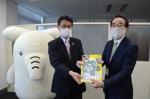 副島浩一郎理事長(左)から教材本を受け取る天野昌明会長=佐賀県庁