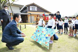 山口知事(左)に手作りのプレゼントを贈る園児=神埼市の神埼こども園
