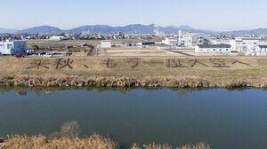 嘉瀬川ののり面に浮かび上がる「来秋、もう一度大空へ」の文字=佐賀市嘉瀬町側からドローンで撮影