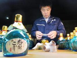 富山県黒部市の酒蔵の設備を借りて日本酒を造り、出荷前のボトルにラベルを貼る加賀の井酒造の小林大祐さん=1日