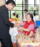 商品を購入した来場客に「ありがとうございます」と笑顔を向ける「小麦の家福祉会」の夏秋さん=佐賀県庁