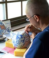 筆先に集中する本島悟さん。「描くときは呼吸を止るぐらいでないとないと思い通りにはいかない」と話す=有田町の今右衛門窯