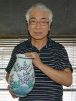 今右衛門窯の作品を手にする天ケ瀬さん。絵の具のすり方や自分に合った筆の作り方など、窯の先輩職人に「一から教えてもらった」と話す