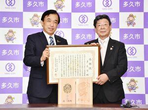 横尾俊彦多久市長(左)に感謝状と記念品を贈った南三陸町の佐藤仁町長=市役所