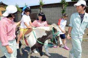佐賀農業高の生徒らにサポートされながらポニーに乗るふたばこども園の年長児=白石町の佐賀農業高