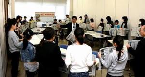 ゲームやクイズなどを通して親子で新聞の役割を学んだ「新聞ワークショップ」。中央が講師の越地さん=佐賀市の佐賀新聞本社