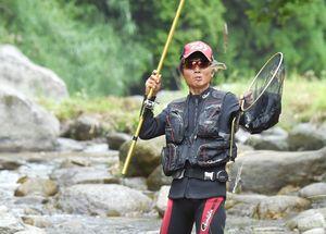 友釣りでアユを釣り上げる男性=15日午前、唐津市の玉島川
