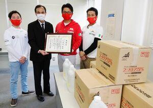売上金で購入した消毒液を佐賀市に贈呈した、ピッツェリア・ダ・ジーノの沖津健代表(右から2人目)=佐賀市役所大財別館