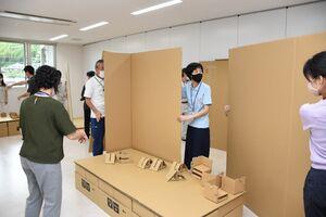 避難所運営訓練で段ボール製のベッドや間仕切りを組み立てる職員=武雄市役所